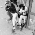 A fan grabs Mays in right field as another player from the bullpen grabs a fan at Shea Stadium on Oct. 10, 1973.