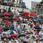 Spectators sit under umbrellas as the match was delayed for rain near the end of the second set.