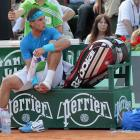 Nadal waits for medical assistance during a changeover.
