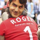 A spectator wears a mask depicting Roger Federer.