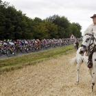 A spectator enjoys a good horse laugh at the peloton's expense during the famed bicycle race...
