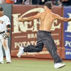 Centerfielder Andres Torres does not seem all that amused by a spectator who got carried away by his zeal, jumped on the field and attempted to show off his chisled physique during a game against the San Diego Padres in San Francisco.