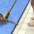 """Using a method that only W.C. Fields could love -- (it was Fields who said, """"Children should not be seen or heard...ever again"""") -- a swimming coach gives his young charge the brush-off at a training center in Beijing. (We kid you not, brooms are actually used to keep tykes from grabbing onto the side of the pool. It's truly sink or swim...)"""