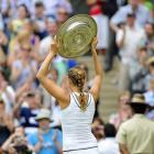 Petra Kvitova raises the trophy to the Centre Court audience.