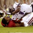 Stanford wide receiver Chris Owusu loses his helmet after being tackled by Washington safety Sean Parker.