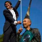 """Television journalist Takashi Yanagisawa holds a measuring tape from atop a step ladder while interviewing Japanese fashion designer Kazuhiro Watanabe, who holds the world record for the """"Tallest Mohawk."""" According to the Guinness World Records, Watanabe's do stands at 3 feet 8.6 inches."""