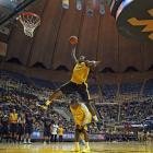 West Virginia freshman center Aaric Murray leaps over senior guard Darryl Bryant during a dunk contest at Mountaineer Madness.