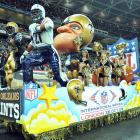 New Orleans cheerleaders ride on a Mardi Gras-style float during the halftime show of the Saints-Chargers regular season game at Wembley Stadium.