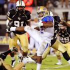 Tulsa running back Trey Watts lands awkwardly after leaping over UCF linebacker Josh Linam. Watts had 63 rushing yards in a 24-17 victory.