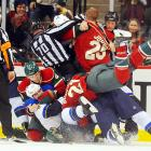 NHL linesman Derek Nansen (70) gets caught in a melee in St. Paul when Wild center Kyle Brodziak (21) was pulled headfirst to the ice by Blues defenseman Roman Polak who was being held by Minnesota defenseman Marek Zidlicky (3). The Wild won 2-1.