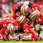 Six San Francisco 49ers pile on Arizona punt returner Patrick Peterson after a fumble. 49ers linebacker Tavares Gooden (56) recovered the fumble in the 23-7 win.