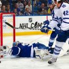 Tampa Bay goalie Dwayne Roloson (bottom) robs Toronto's Tyler Bozak with his glove hand. The Maple Leafs had plenty of other chances, though, and won 7-1.