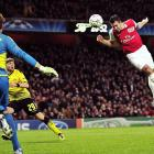 Arsenal striker Robin Van Persie heads in a goal during a UEFA Champions League match against Borussia Dortmund. Arsenal won 2-1.