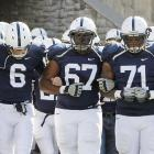 The Penn State players took the field arm-in-arm for their final home game this season without head coach Joe Paterno or wide receivers coach Mike McQeary.