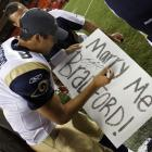 Rams quarterback Sam Bradford signs a marriage proposal sign in 2011 at Arrowhead Stadium after St. Louis beat the Kansas City Chiefs. Hopefully the fan didn't take the signature as a yes.