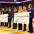 Summit stands with a 75,000 check to support Alzheimer's research. In August of 2011 she was diagnosed with Alzheimer's type early-onset dementia. Summit has 1,071 career victories. She's one of only three college coaches to reach 1,000 wins in any sports and leads all men's and women's collegiate basketball coaches.