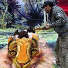 An artiste and three models in Fuzhou, Fujian province found a novel way to increase awareness of the need to protect endangered animals from people who run amok with brushes and paint. For his next act, the artiste will paint a human on the backs of three tigers, assuming he can get them to sit still long enough.