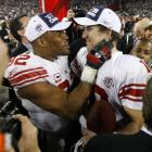 Manning and legendary defensive end Michael Strahan celebrate after improbably beating the previously undefeated Patriots 17-14 in Super Bowl XLII.