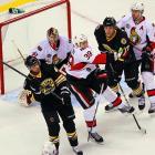 Senators' defenseman Matt Carkner battles with a pair of Bruins in front of Ottawa's net.