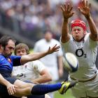 France's Julien Dupuy, left, kicks the ball as England's Mouritz Botha tries to block it during their six nations rugby match at the Stade de France stadium.