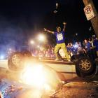 Back in Lexington, celebrators told AP the mayhem was worse following the national semifinal win over Louisville, as this Saturday photo suggests. More than two dozen arrests were made that night. The AP reported that firefighters were dispatched to 50 blazes near the Lexington campus, which included a car, couches and campfires that were lit in the middle of the street.