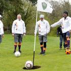 A good walk spoiled by big (mostly white) balls: the former French soccer star (second from right) wonders why his birdie putt continues to hover above the cup at the Golfoot Masters in Lausanne, Switzerland.