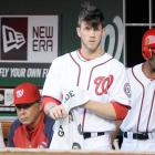 Harper watches the action from the dugout during a game against Arizona.
