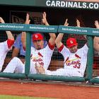 Jaime Garcia, Kyle Lohse, Daniel Descalso and Tony Cruz indicate that catcher Yadier Molina's 35-yard field goal attempt against Chicago is good during the third inning at Busch Stadium.