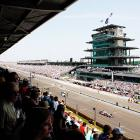 Cars race down the frontstretch past fans in the grandstands.