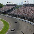 Cars race past a grandstand full of fans.