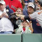 Mark Reynolds of the Baltimore Orioles goes for a foul ball while playing the Boston Red Sox, but a New England Patriots fan gets it first.