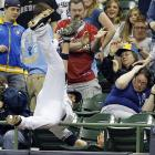 Fans show a range of emotions as Milwaukee's Travis Ishikawa leaps into the seats to catch a foul ball off the bat of Cincinnati's Ryan Ludwick.