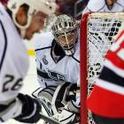 Kings goalie Jonathan Quick keeps a close watch on Devils forward Stephen Gionta as he carries the puck behind the net.