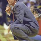 Riley squats on the sideline during a regular season game against the Boston Celtics. Riley faced the Celtics in three NBA Finals during his Lakers tenure and won two of those series.