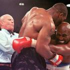 Referee Lane Mills steps in to separate the two boxers after Tyson bit Holyfield's ear in the third round.