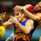 Ryan Harwood of the Lions gets dragged down by James Magner of the Demons as they compete for a mark during an Australian Rules Football match on July 1.