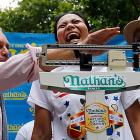 """Sonya (The Black Widow) Thomas stands on a scale as she's weighed by New York City Mayor Michael Bloomberg (L) during the official """"weigh-in"""" FOR THE annual Nathan's Famous Coney Island 4th of July Hot Dog-Eating Contest. The photo was shot at New York's City Hall Park on July 3."""