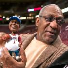 """Bill Cosby holds a """"Fat Albert"""" bobblehead doll before the start of a 2004 76ers-Bucks game in Philadelphia."""