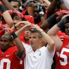 """College football is rich in stirring tradition. Here we have head coach Urban Meyer leading his players as they ask the musical question """"What's hi in the middle and round on the ends?"""" after beating Miami of Ohio, 56-10, in Columbus, which is in Ohio, which is, of course, hi in the middle and round on the ends, hence the stirring tradition."""
