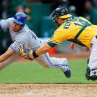 Oakland Athletics catcher George Kottaras tags out Moises Sierra of the Toronto Blue Jays.  The Blue Jays beat the Athletics in Oakland, 6-5, to split the four-game series.