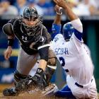 Kansas City's Alcides Escobar creates a dirt storm while sliding past the tag of Chicago White Sox catcher Tyler Flowers.