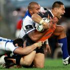 Canterbury Bulldogs players struggle to bring down Matt Utai of the Wests Tigers during a National Rugby League match.