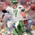 Boomer Esiason is grabbed from behind by Henry Ford of the Houston Oilers for a 12-yard loss in the 1995 matchup.