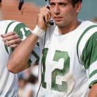 Joe Namath talks to a coach upstairs from the sidelines of a game against the Broncos at Bears Stadium.