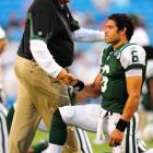 Mark Sanchez shakes hands with head coach Rex Ryan as he stretches before a game.