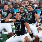 Linebacker Lance Williams (center) and his teammates tried to scare the hell out of Lamar with a hearty haka before their game in Honolulu and apparently succeeded. Final score: Hawaii 54, Lamar 2.