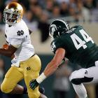 """Everett Golson made plays with his arms and legs, and an inspired Manti Te'o helped Notre Dame's defense smother Michigan State. The Fighting Irish are off to their best start in 10 years, with the type of marquee victory that's eluded them for almost as long. Golson (left) threw a touchdown pass and ran for a score in the first half to help the Fighting Irish dominate the Spartans. The Irish (3-0) snapped a six-game losing streak against ranked teams and beat a top-10 opponent for the first time in seven years. """"It's a signature win,"""" third-year Notre Dame coach Brian Kelly said."""