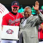 """On September 28, a day dubbed """"Chipper Jones Day"""" by the governor of Georgia, Atlanta honored their third baseman. Teammates gave him a pool table. The Braves organization added a number of gifts, topped off with a Hawaiian vacation. The bases and on-deck circles for the team's final home stand are stamped with the Chipper Jones logo (as seen in the photo of Jones and Hall of Famer Hank Aaron) and will be auctioned off for charity."""