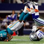 Dallas wide receiver Saalim Hakim and Miami Dolphins cornerback Vince Agnew get tangled during the second half of an NFL preseason game.