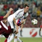 FC Basel's Marco Streller (center) and CFR Cluj's Cadu (left) collide, sending the ball and Streller's hair flying.